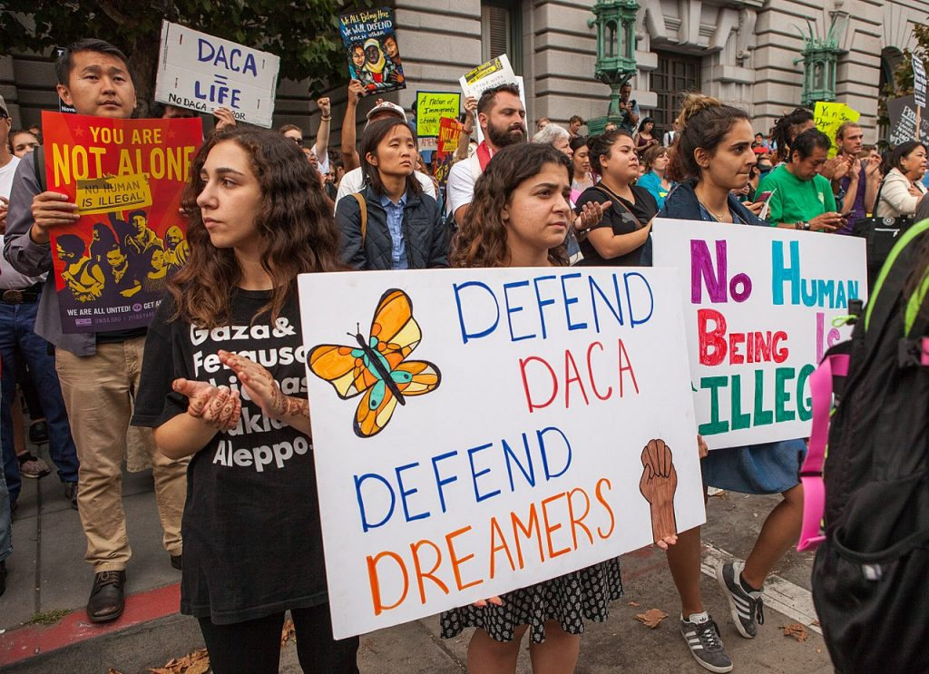 An image of protesters hold various signs and banners at a DACA rally in San Francisco. Sept. 5, 2017 by Pax Ahimsa Gethen. Used under CC BY-SA 4.0 (https://commons.wikimedia.org/wiki/File:DACA_rally_SF_20170905-8471.jpg)