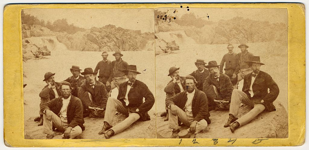 Stereograph showing group of early Secret Service officers seated on a rock by a river. Library of Congress.