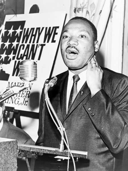 An image of Martin Luther King, Jr., three-quarter-length portrait, standing, facing front, at a press conference by Walter Albertin, June 8, 1964. Source: Library of Congress