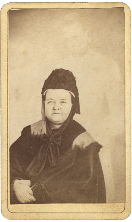 """Mary Todd Lincoln with Abraham Lincoln's 'spirit.'"" An image of Mary Todd Lincoln, seated, head and torso, hands in lap, wearing mourning gown and bonnet, with spirit figure of Lincoln behind her resting his hands on her shoulders by William H. Mumler circa 1872. Source: Lincoln Financial Foundation Collection, Allen County Public Library, Fort Wayne, Indiana"