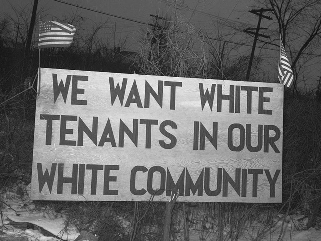 "Detroit, Michigan. Riot at the Sojourner Truth homes, a new U.Sn federal housing project, caused by white neighbors' attempt to prevent Negro tenants from moving in. Sign with American flag ""We want white tenants in our white community,"" directly opposite the housing project. Source: Library of Congress"