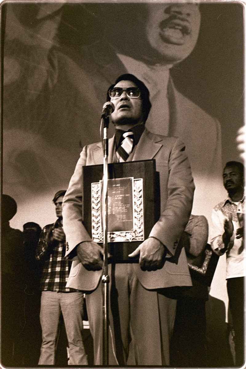 Jim Jones on a stage before a microphone, holding an award placard. MLK is projected on a wall in the background.