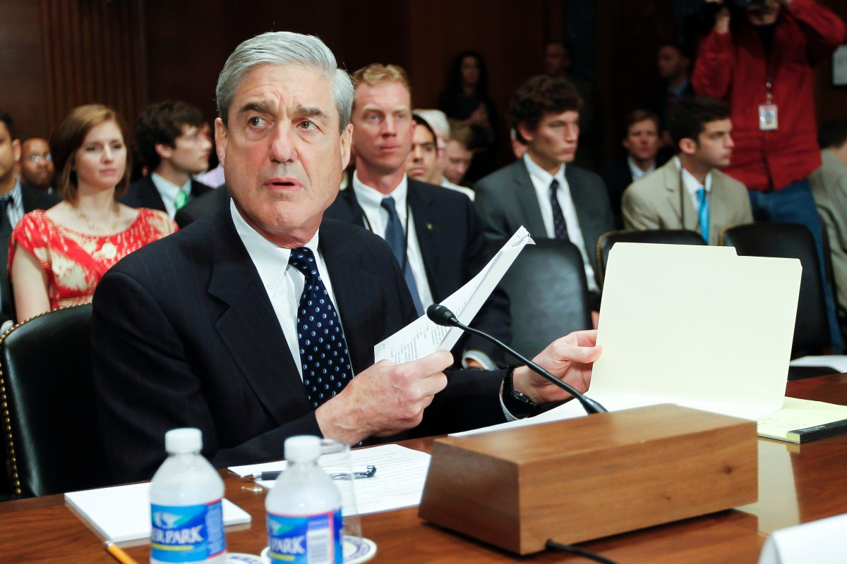 Robert Mueller sits at desk testifying in front of Congress. Colorized. Mueller is in front of a microphone in a suit and tie.