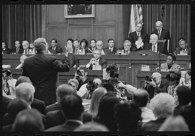 Black and white photo. Ken Starr has his right hand up and is swearing in before Congress. Numerous cameras and Congressmen look at Ken Starr. Picture is from behind Ken Starr and facing the Congressional committee.