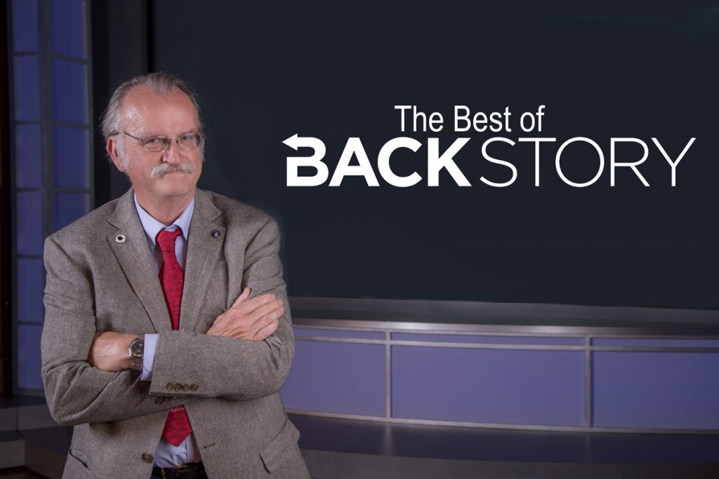 "Peter Onuf, arms crossed, stands in from of a wall with ""The Best of BackStory"" on it."