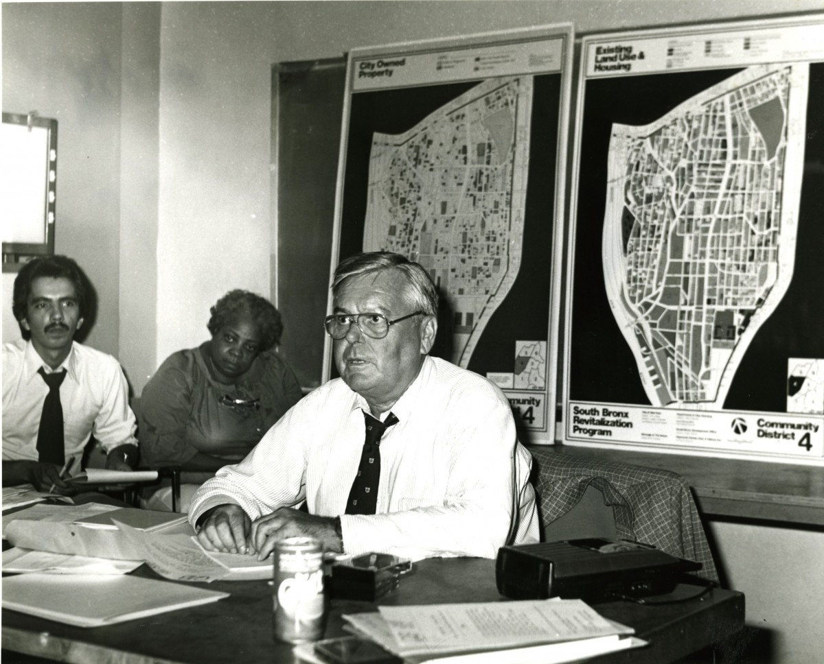 Ed Logue seated at a table in front of maps.