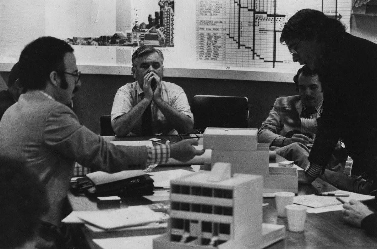 Logue and others seated around a table holding miniature models of buildings.