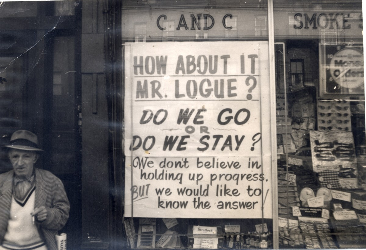 "A sign in a shop window reads ""How About it Mr. Logue? Do we Go or Do We Stay?"""