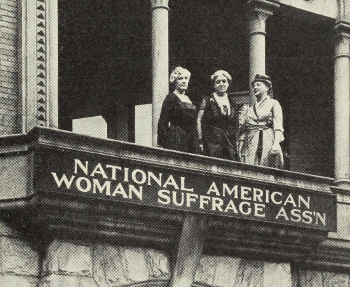 "Helen Hamilton Gardener, Carrie Chapman Catt and Maud Wood Park stand on a balcony over a banner that reads ""National American Woman Suffrage Ass'n"""