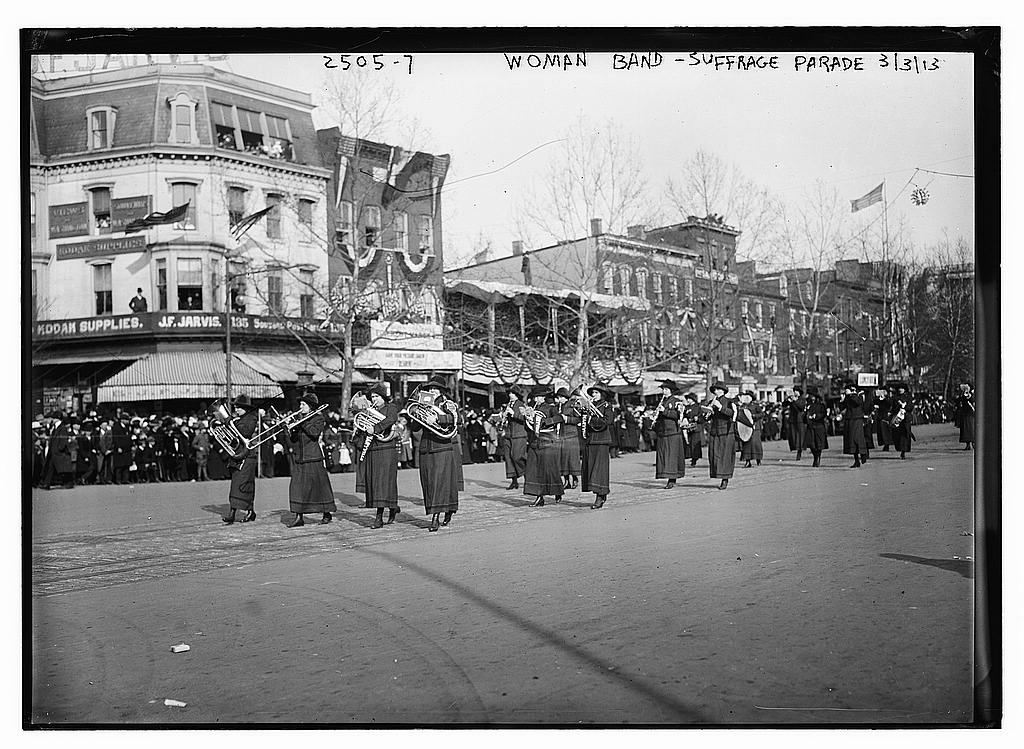A marching band marching down a spectator-lined street.