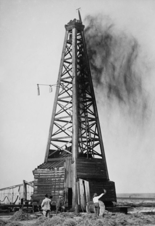 Workers stand beneath large wooden oil well structure, cloud of oil droplets hangs overhead.