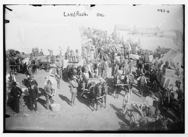 Settlers with horses and wagons stand waiting among large tents.
